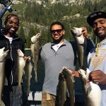 Three anglers holding multiple trout